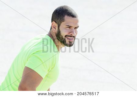 Closeup portrait of content young handsome strong man looking away with blurred view in background