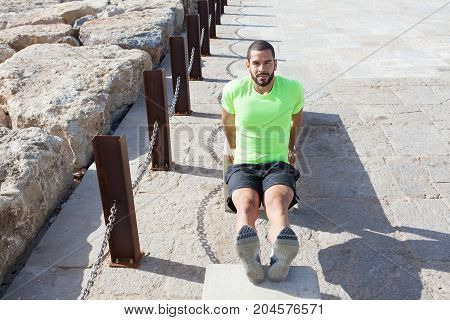 Portrait of content young strong handsome man wearing sportswear, looking at camera and doing triceps dips on concrete benches in city. High angle front view.