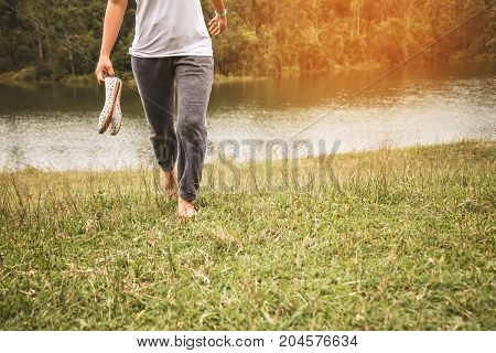 Asian women relax in the holiday. Walking foot on the meadow