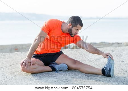 Serious young handsome strong man wearing sportswear, sitting on concrete ground and stretching leg with river in background