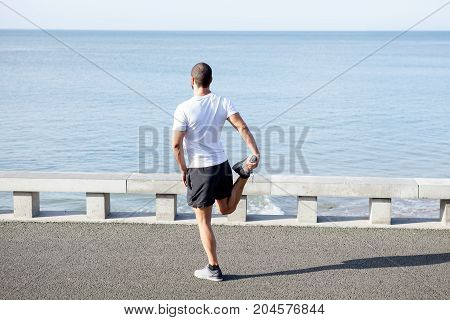 Young muscular sporty man wearing sportswear, standing on one leg on bridge and stretching other leg with sea in background. Back view.