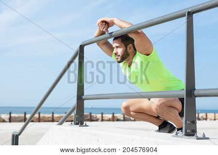 Portrait of young handsome strong man wearing sportswear, looking away, relaxing, sitting on hunkers and leaning on railing at seaside
