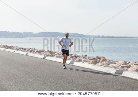 Serious young strong man wearing sportswear and running on seaside road with sea in background