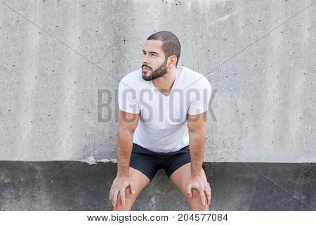 Closeup portrait of young handsome strong man wearing sportswear, looking away, leaning on wall and knees. Front view.