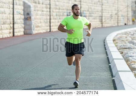 Portrait of serious young strong man wearing sportswear and running on road with stone wall in background. Front view.