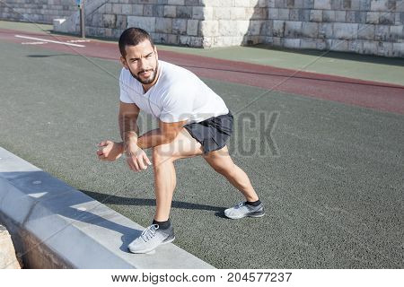 Content young strong handsome man wearing sportswear, standing on road and curb, stretching calf and leaning on knee with stone wall in background