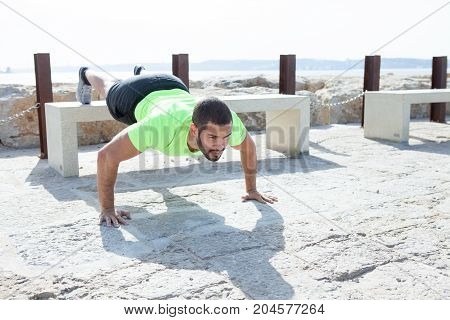 Portrait of focused young strong handsome man wearing sportswear and doing feet elevated push-ups on concrete bench at seaside