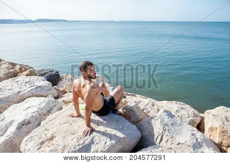Pensive young handsome strong man looking away and sitting on stones on sea shore. Back view.