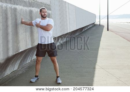 Serious young handsome strong man wearing sportswear, standing, leaning on concrete wall and stretching arm