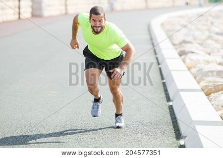 Portrait of tensed young strong man wearing sportswear and running fast on road. Front view.