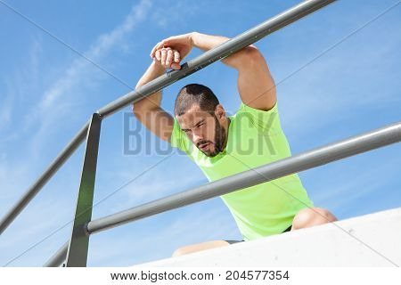 Portrait of young handsome strong man wearing sportswear, looking away, relaxing, sitting on hunkers and leaning on railing at seaside. Low angle view.