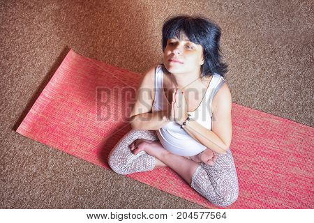 Pregnancy Yoga and Fitness concept. Healthy maternity lifestyle concept. 40 week pregnant middle aged caucasian woman sitting in lotus asana doing yoga exercise top view