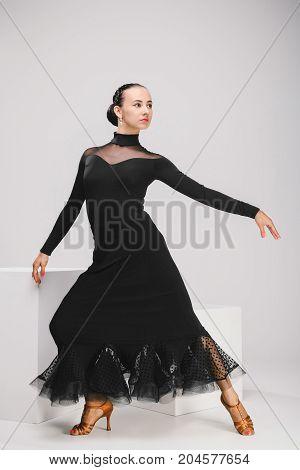 pretty girl in black dress in studio, dancer posing and looking back