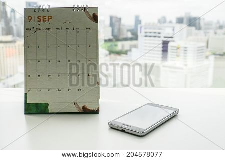 mock up September calendar with smart mobile phone for business appointment