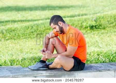 Concentrated handsome athlete texting sms on phone while sitting on concrete slab outdoors. Serious sporty man finding information on Internet in park. Technology concept