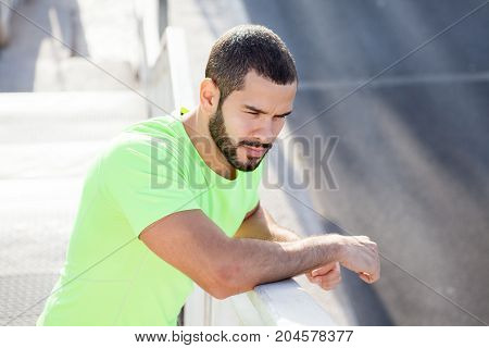 Contemplative handsome fitness trainer being on stroll. Aspirated young man in green t-shirt leaning on railing and looking at road outdoors. Deep in thoughts concept