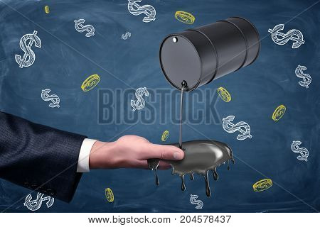 A businessman's hand reaching out to catch oil leaking from a small black barrel. Oil and gas industry. Catch you profit. Easy income.