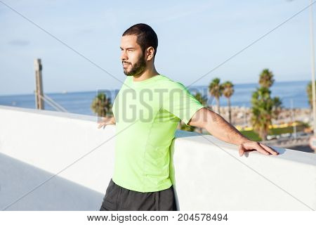 Pensive free man enjoying summer vacation and looking around. Confident handsome athlete building up strength while walking alone. Aspirations concept