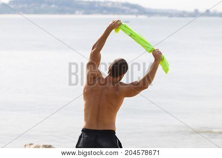 Closeup of shirtless young handsome strong man holding t-shirt, stretching body and doing side bend exercise with sea in background. Back view.