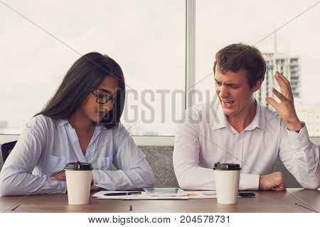 Annoyed businessman arguing with colleague at meeting. Frustrated young executive crying at Indian female assistant while they working on project in board room. Dissatisfaction concept