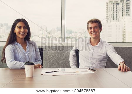 Cheerful successful colleagues working as team. Happy confident young multiethnic business partners looking at camera while sitting at table with papers in office. Collaboration concept