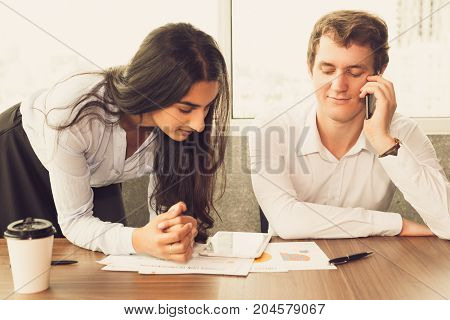 Indian assistant proving report to boss and waiting when he stopping talking on phone. Smiling young businessman listening to partner and looking through paper. Busy day concept