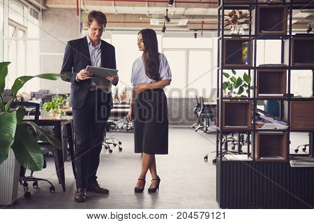 Modern multiethnic business people working on project and using tablet to look through file in office. Confident managers standing in open plan office while discussing strategy. Teamwork concept