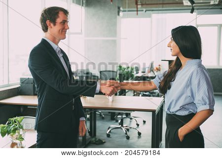 Pleased male manager greeting with new colleague and shaking hand of Indian businesswoman. Confident business coworkers congratulating each other with beginning of collaboration. Partnership concept