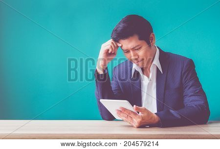 Businessman Sitting At Wood Table And Green Wall And Looking Down At Tablet Computer Screen At Offic