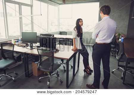 Puzzled business people thinking of new plan in empty office. Confident young Indian woman offering strategy for business development while talking to colleague in open plan office. Company concept