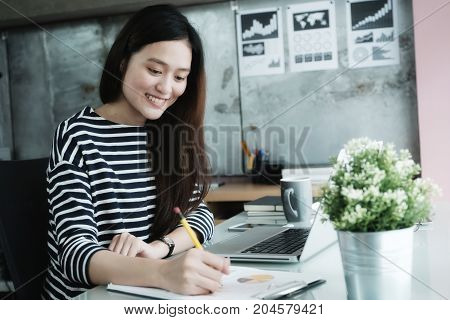 Young asian office woman working with laptop computer at desk office background Office lifestyle concept