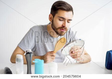Morning hygiene routine of a guy shaving brushing and flossing teeth