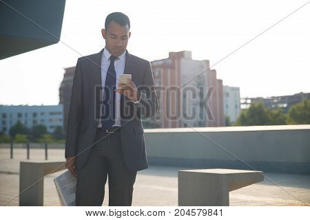 Concentrated young businessman in suit holding newspaper and using smartphone. Executive manager checking mailbox or reading message in street. Wireless connection concept