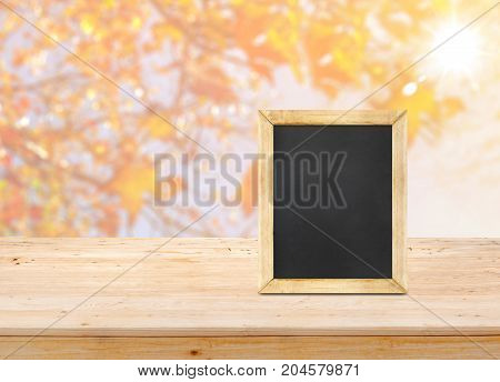 Blackboard on wood table top with blur maple leaf with sunlight backgroundAutumn backdropMock up for display or montage of productbanner for advertise on online.