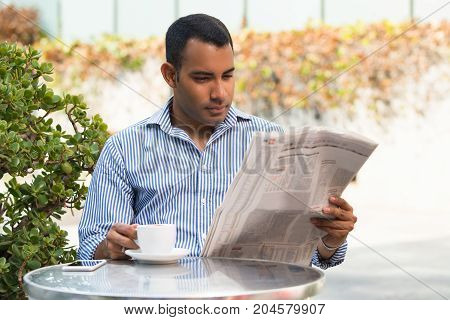 Concentrated Hispanic young man sitting in outdoor cafe, reading newspaper and drinking coffee. Executive manager reading recent news during lunchtime. Business news concept