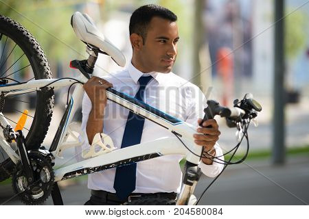 Handsome Hispanic businessman wearing white shirt and tie carrying his bike. Young male office worker with bicycle out of repair. Accident concept