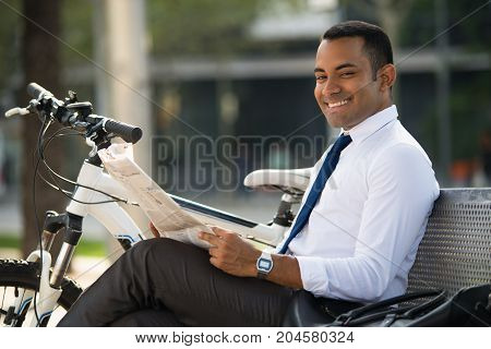 Happy young office worker sitting on bench, holding newspaper, smiling at camera, bike nearby. Hispanic businessman resting in park during lunchtime