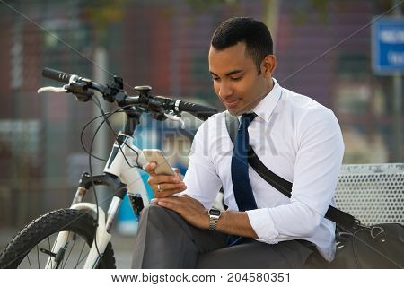 Happy Latin businessman sitting on bench, bike nearby, using mobile phone. Smiling young office worker reading or texting message. Modern technology concept