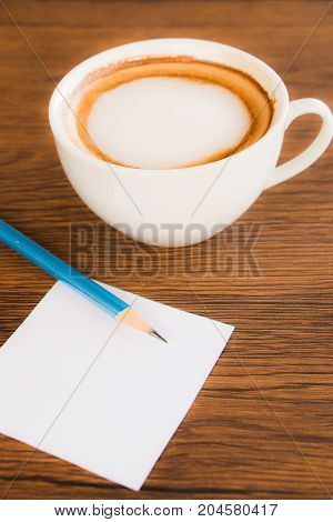 Cup of cappuccino coffee with pencil and blank white paper put on brown wooden table top