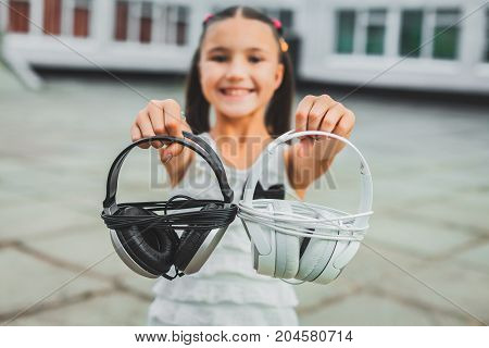 Pretty little teen holding white and black headphones, Cute girl dressed in a white blouse with a black bow and looks at the camera