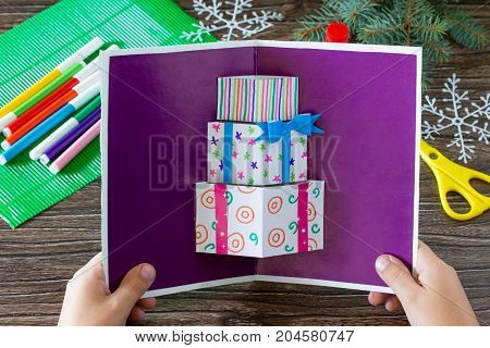 A Child Holds A Birthday Card With Christmas Presents. Made By Own Hands. Children's Art Project, Cr