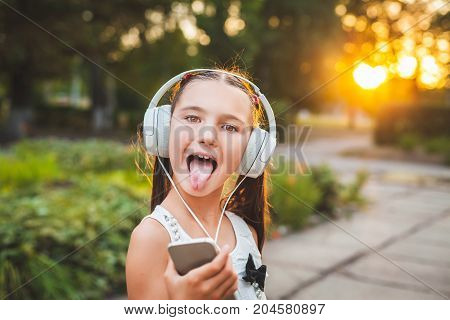 joy girl listening music on the telephone, funny teenager in white headphones at sunset, child and hi-tech concept