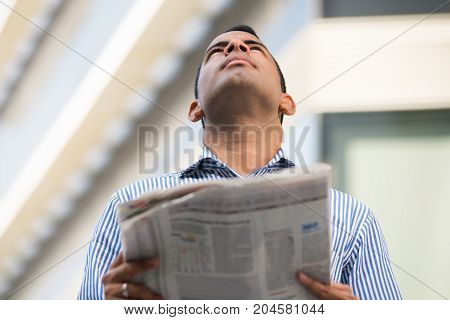 Portrait of serious Hispanic young man standing outdoors, holding newspaper, looking upwards. Business concept
