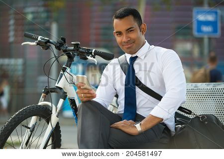 Handsome Hispanic businessman with phone sitting on bench in park, bike nearby. Smiling young office worker using smartphone. Modern technology concept