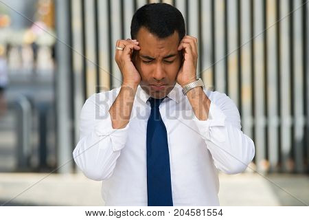 Stressed Latin businessman with closed eyes holding his head with hands. Young office worker suffering from headache. Business challenges concept