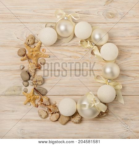Christmas and New Year. Christmas wreath of Christmas-tree white toys in marine style shells stones and starfish. Selective focus.