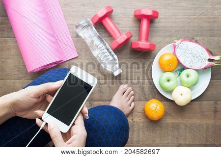 Healthy woman using smartphone before workout and yoga Sport equipments water and fruits on the floor