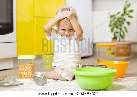 Playful child toddler with face soiled flour. Little boy surrounded kitchenware and foodstuffs