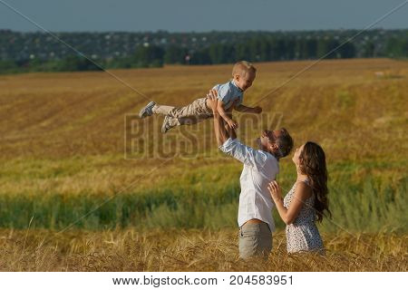 Young Parents And Kid Walking Through Wheat Field