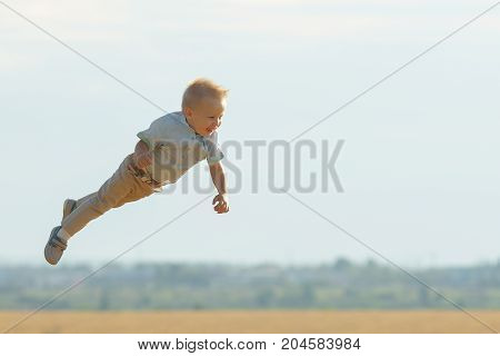 Smiling Boy Flying In The Air, Playing On Field